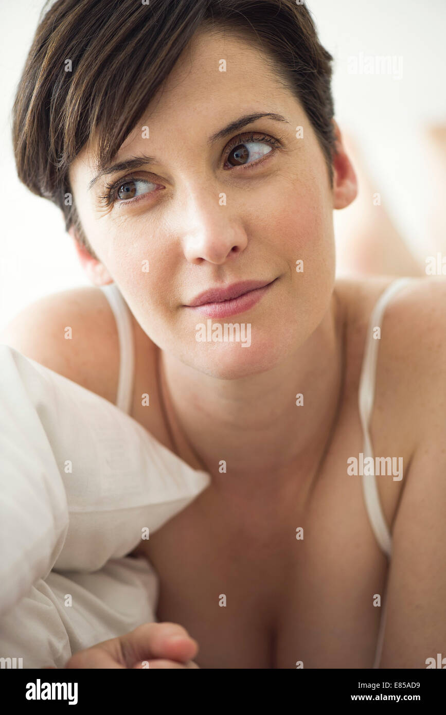 Woman lying on bed contemplating her private future - Stock Image