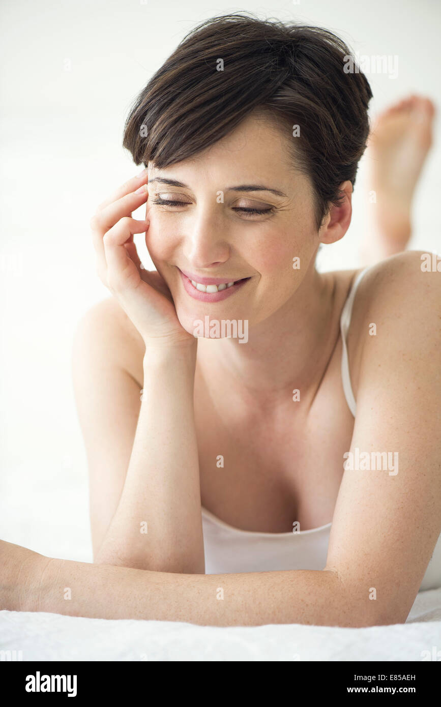 Woman lying on bed with look of contentment, portrait - Stock Image