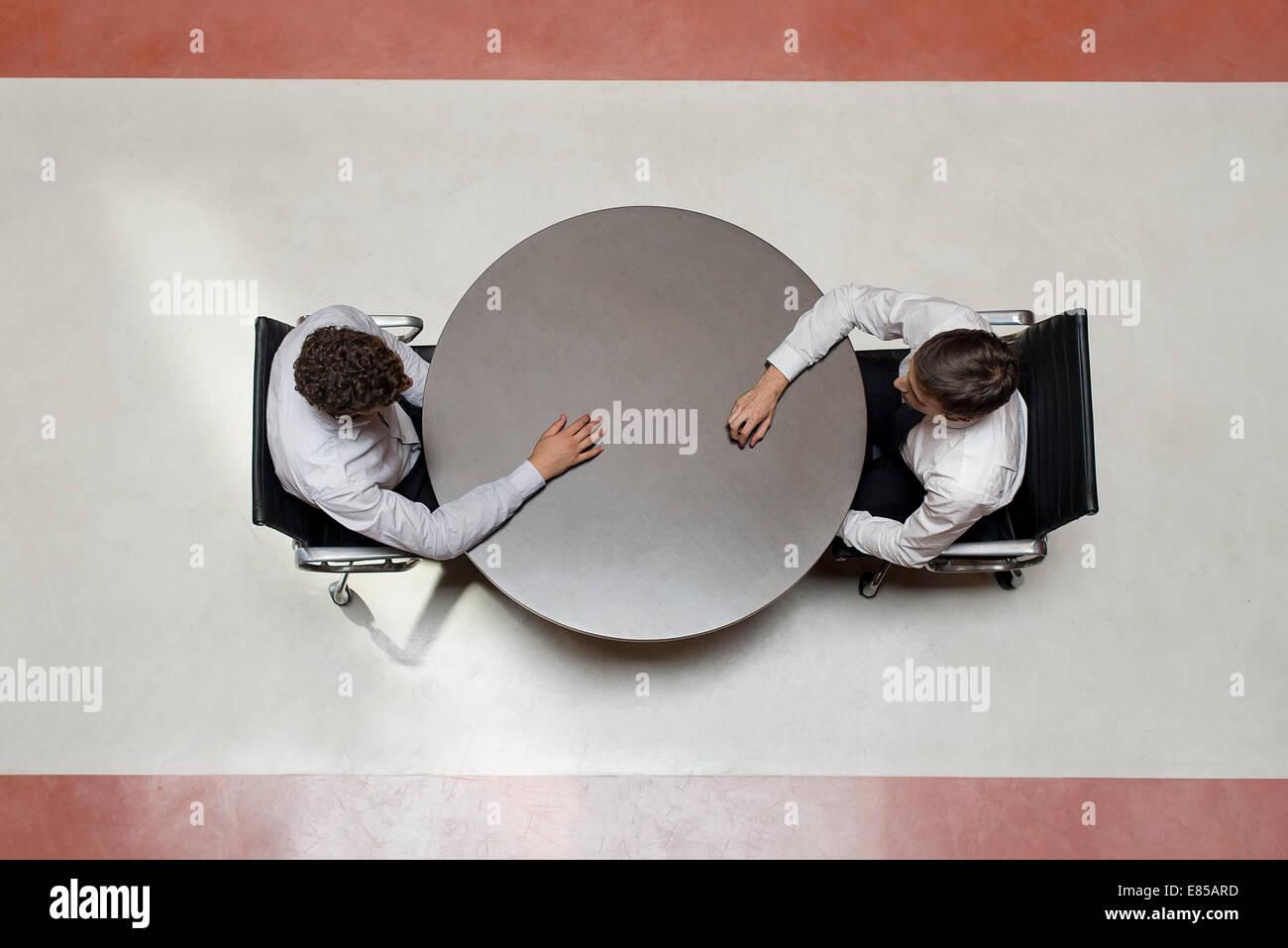 Businessmen stting opposite each other - Stock Image