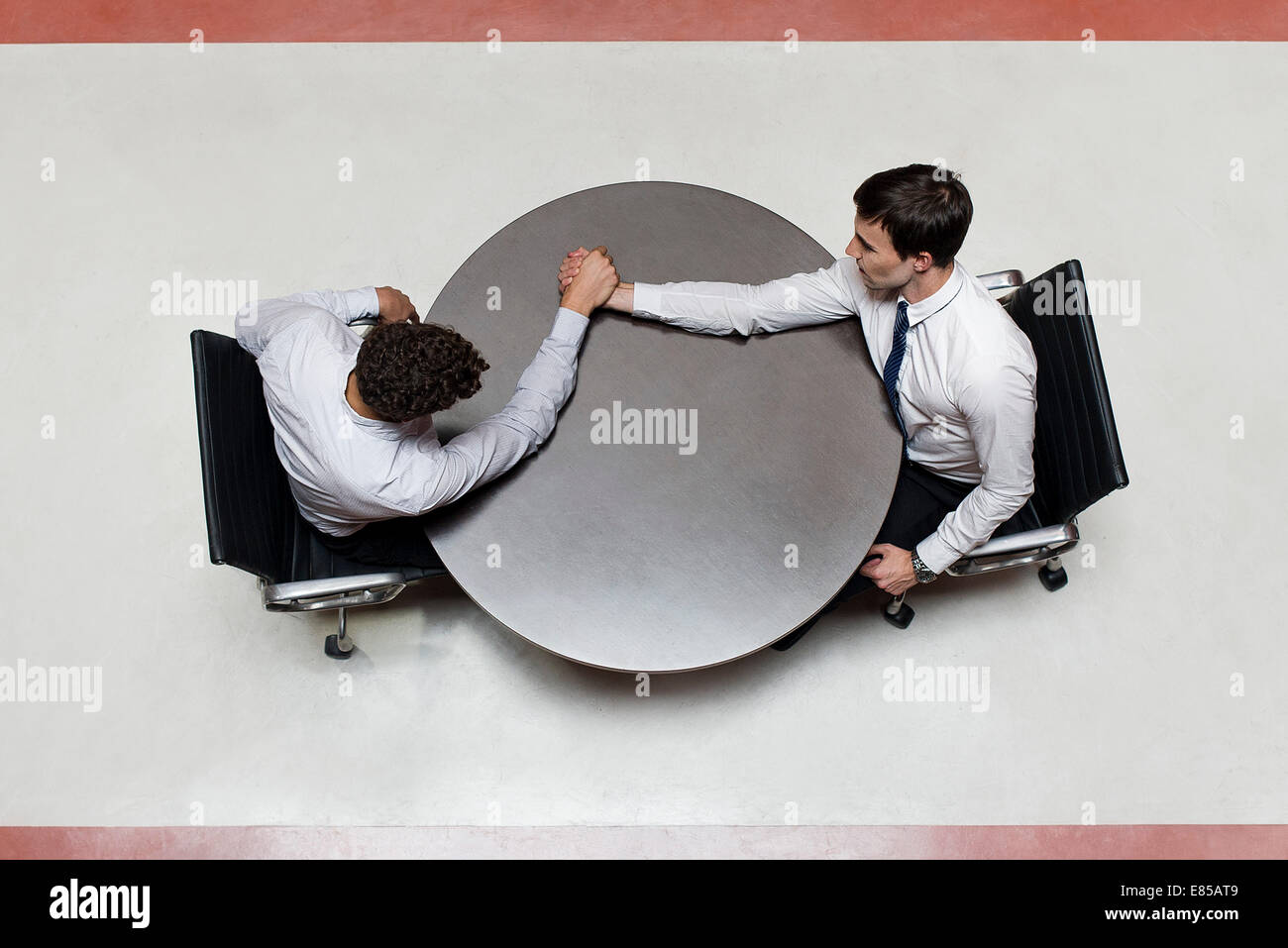 Businessman defeats colleague at arm wrestling match - Stock Image