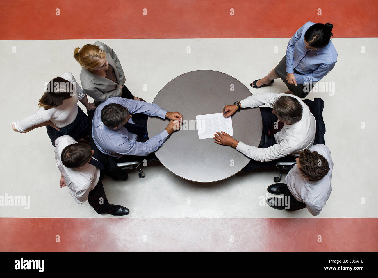 Businessmen flanked by support staff negotiate contract - Stock Image