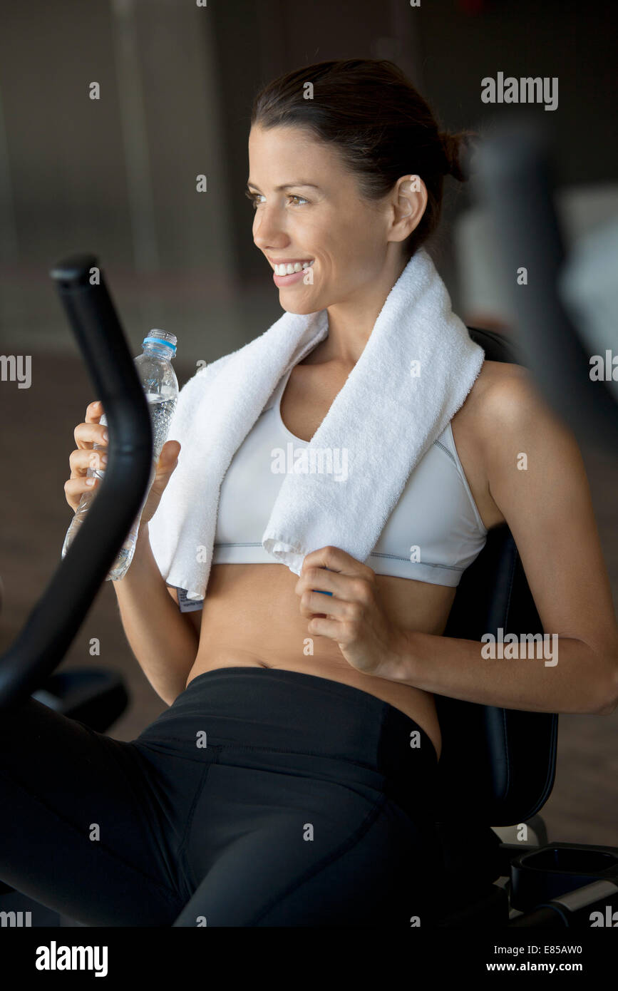 Woman drinking bottled water in health club - Stock Image