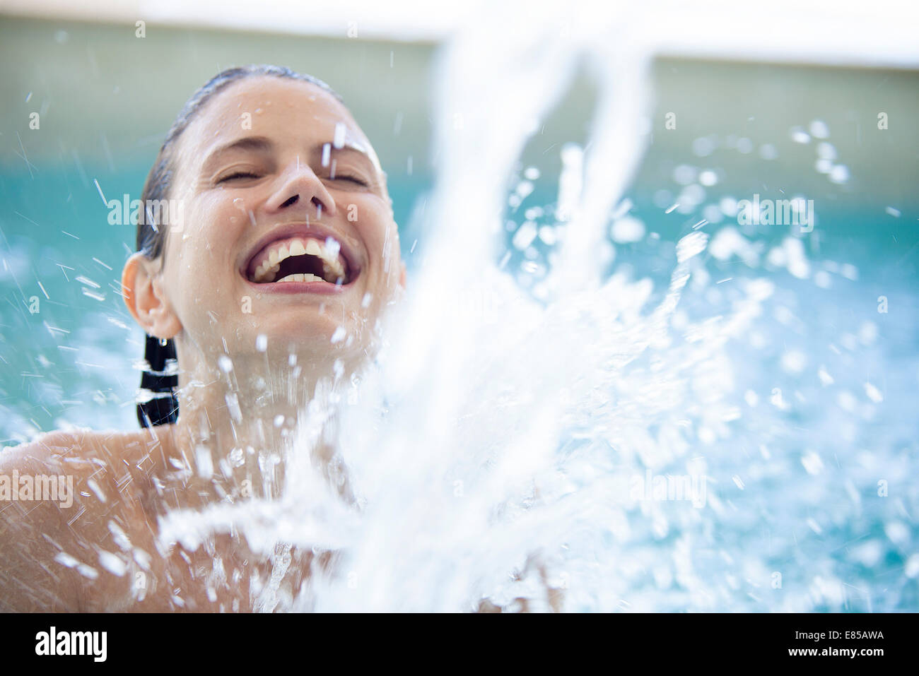 Woman splashing in pool with eyes closed - Stock Image