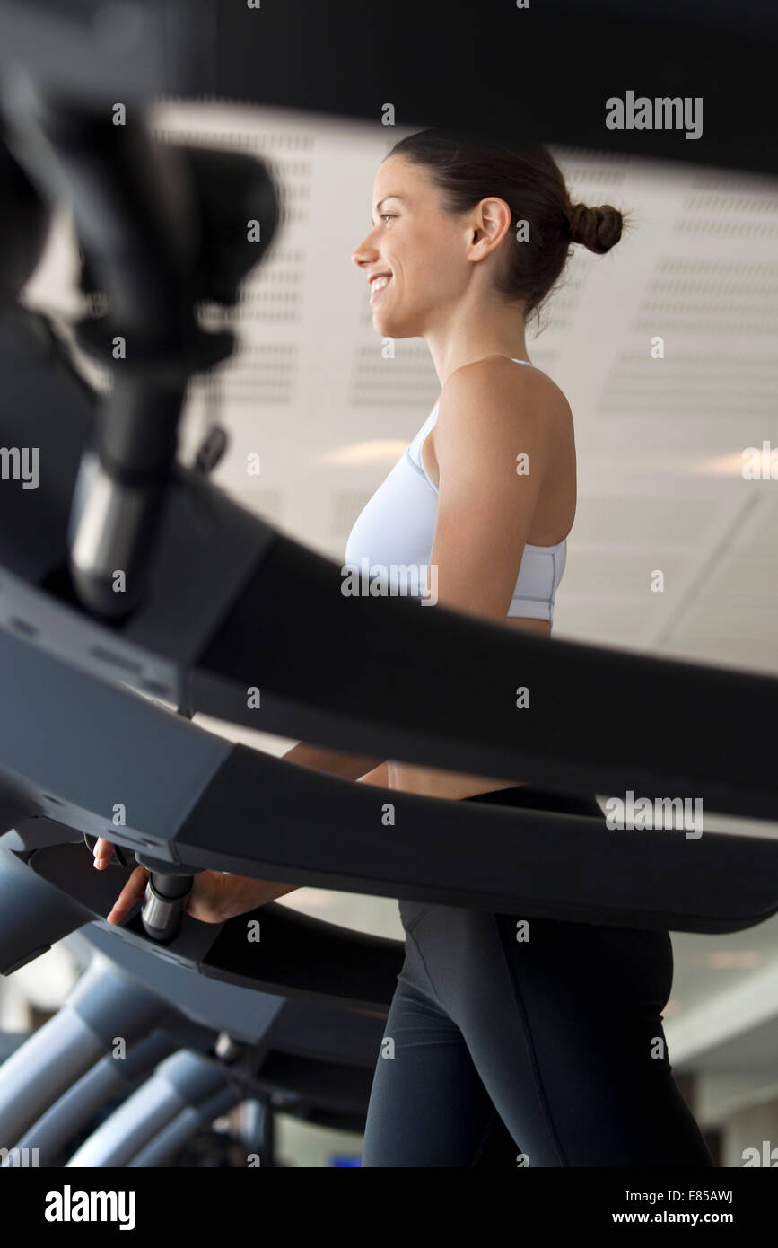 Woman on exercise machine at gym - Stock Image