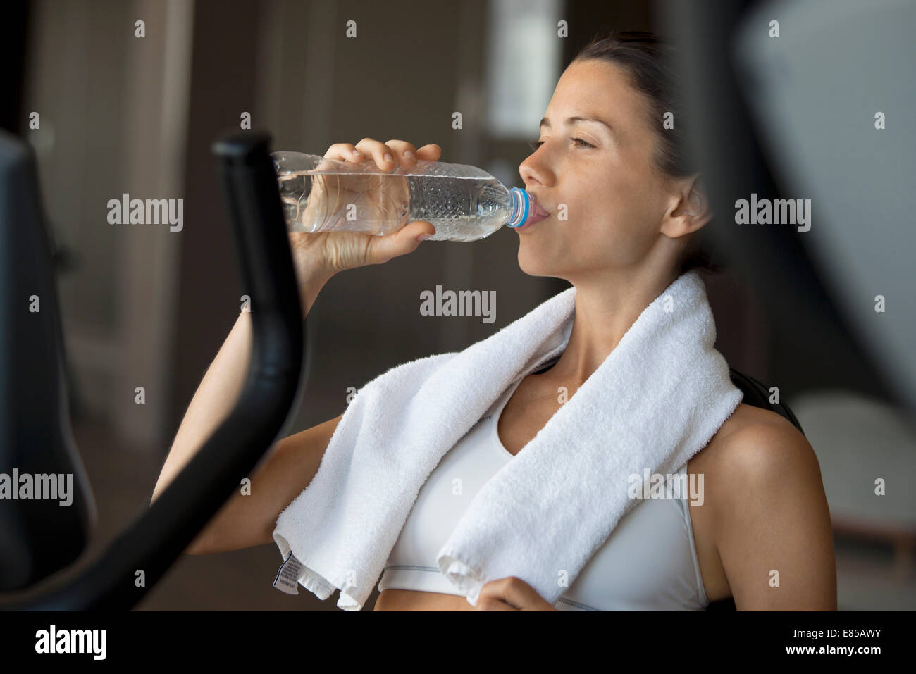 Woman drinking water in health club - Stock Image