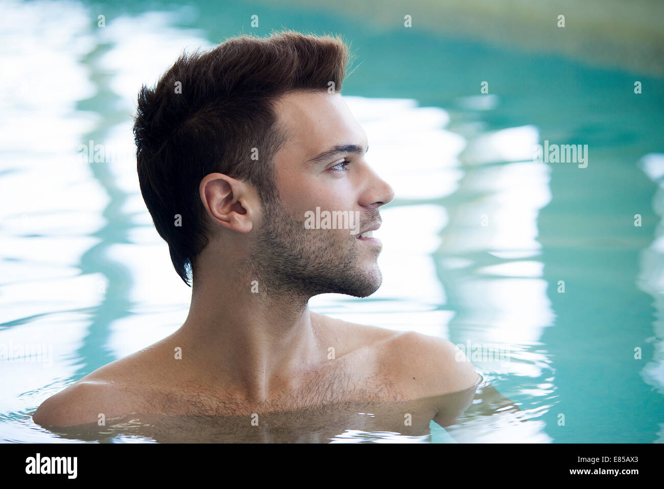 Young man relaxing in pool - Stock Image