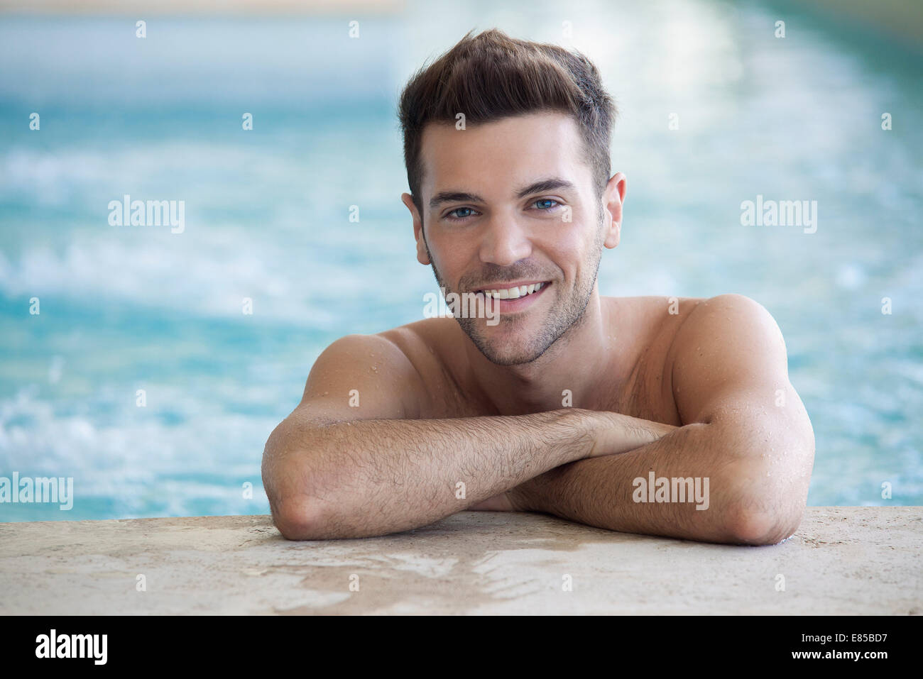 Young man in pool resting against wall - Stock Image