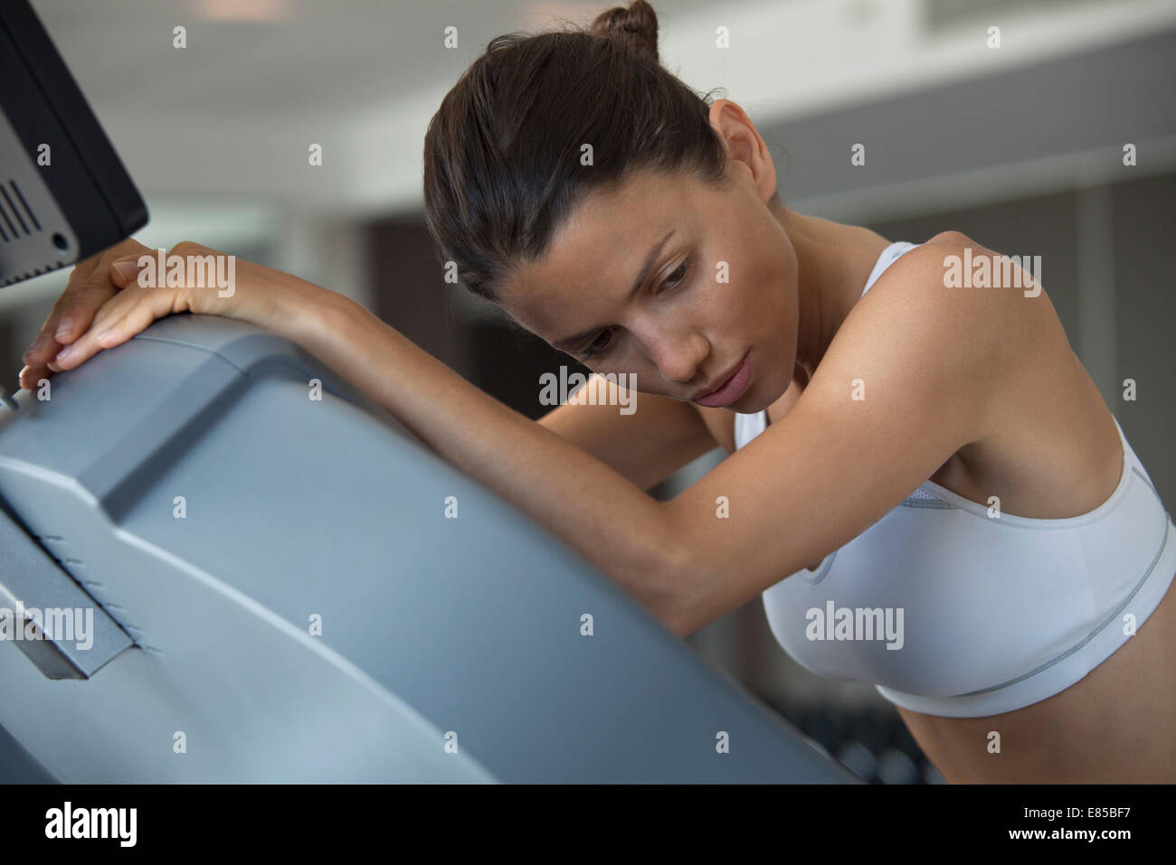 Woman resting on exercise machine in health club - Stock Image