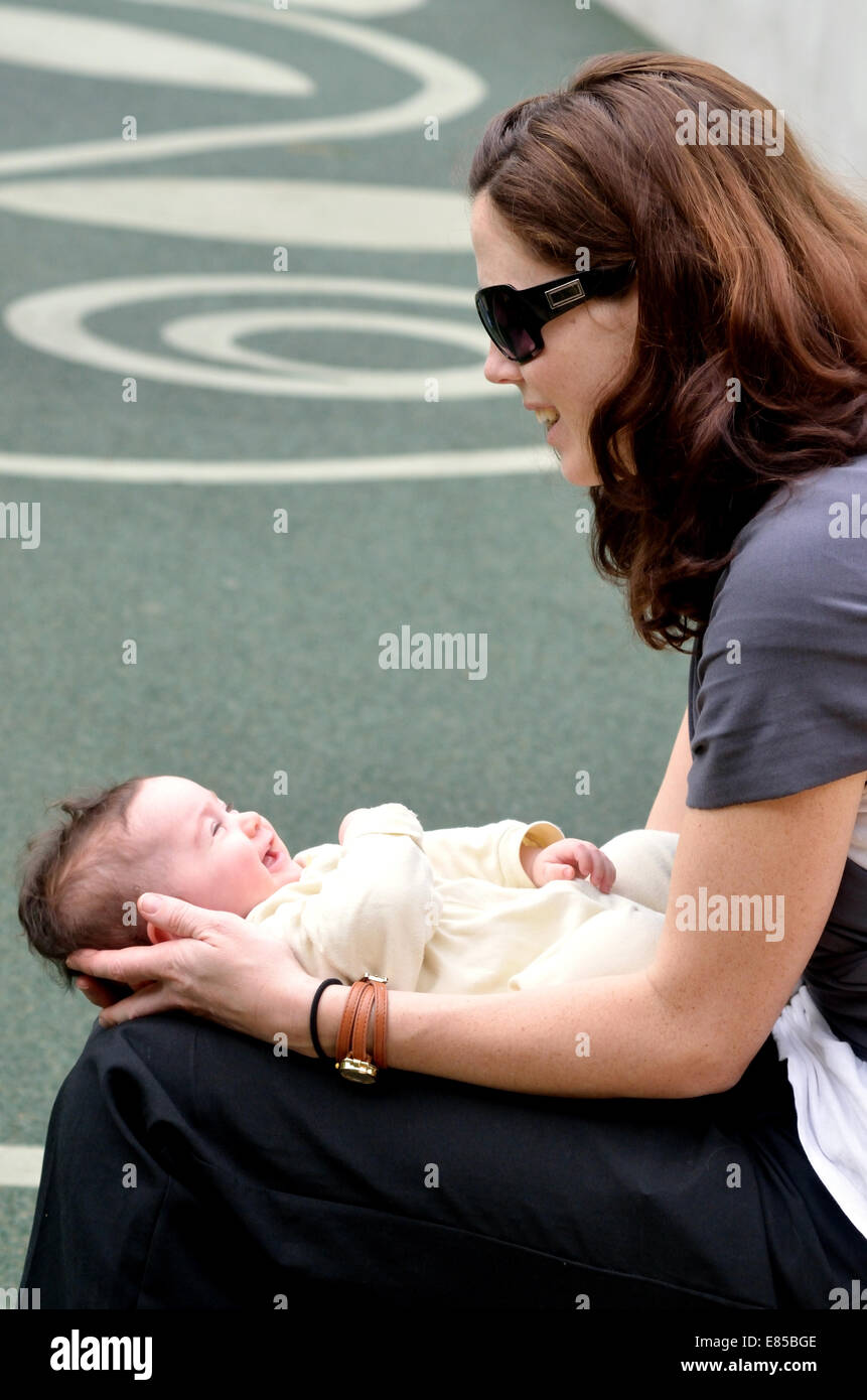 Young mother play with her toddler baby outdoor. Concept photo of, child care, childhood, motherhood, newborn, infant - Stock Image
