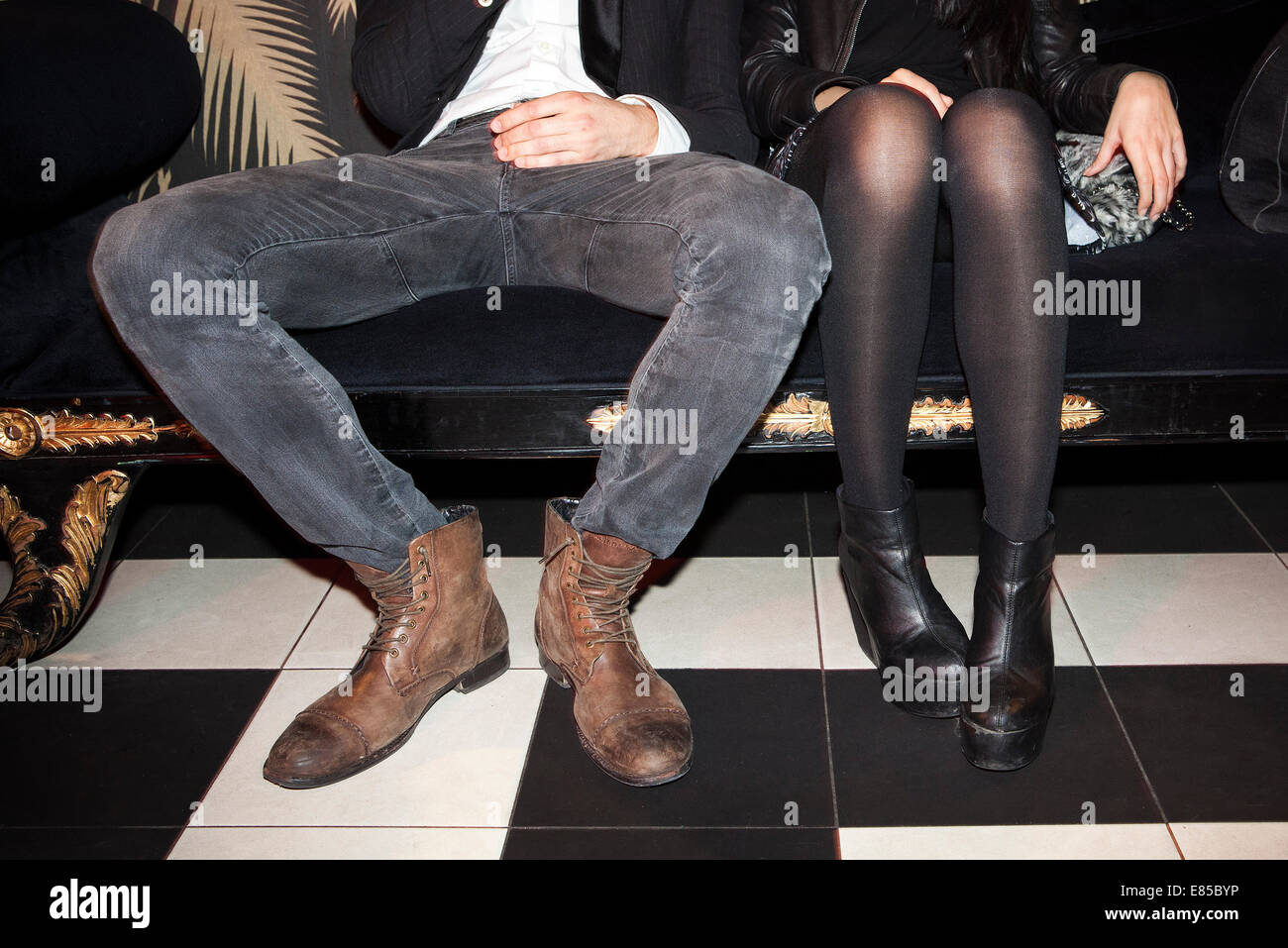 Young couple sitting side by side at night club - Stock Image