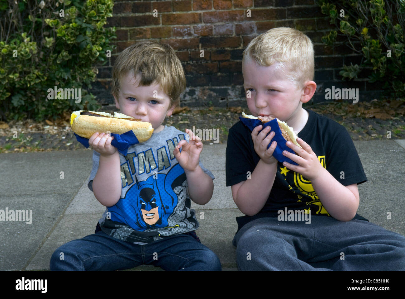 2 youngsters eating hot dogs at the Farnham Food Festival 2014, Castle Street, Farnham, Surrey, UK. - Stock Image