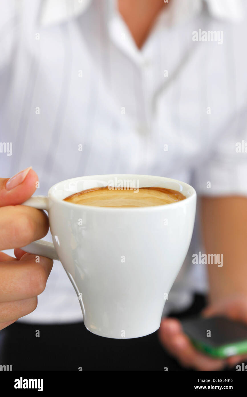 Female holding a cup of coffee - Stock Image