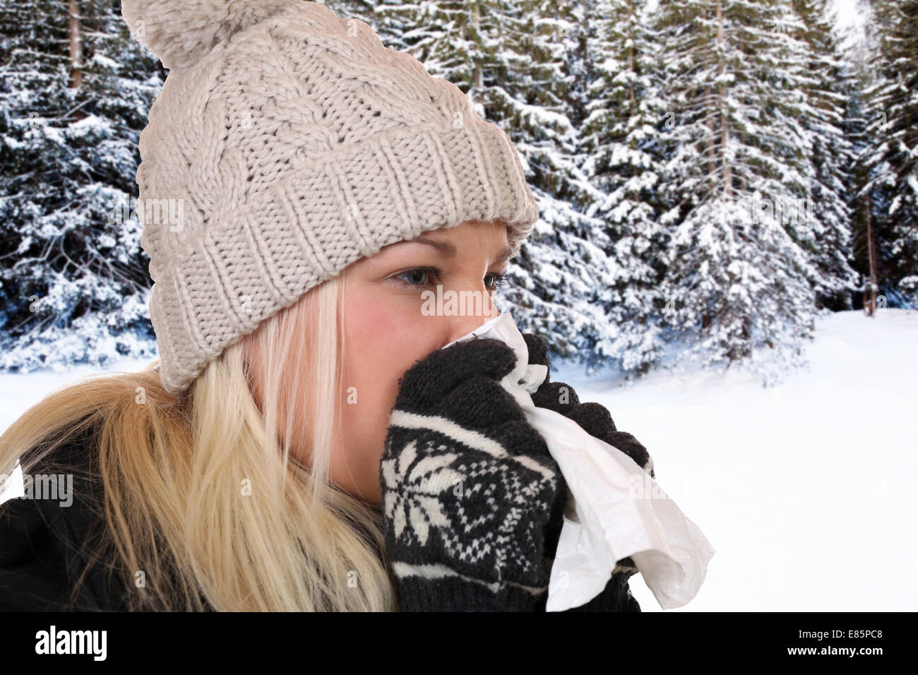 Young woman with a cold and flu virus sneezing into a tissue is ill outdoors - Stock Image