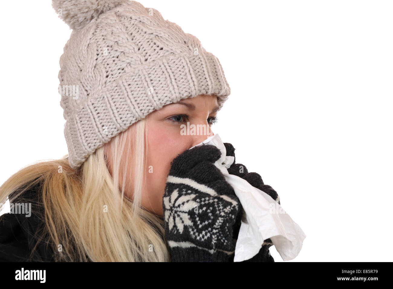 Young woman with a cold and flu virus sneezing into a tissue is ill, isolated on a white background - Stock Image