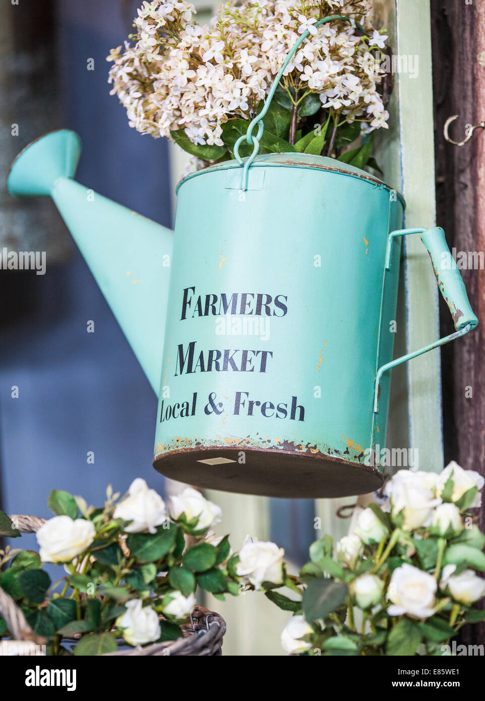 A decorative watering can with 'farmer's market' painted on the side - Stock Image