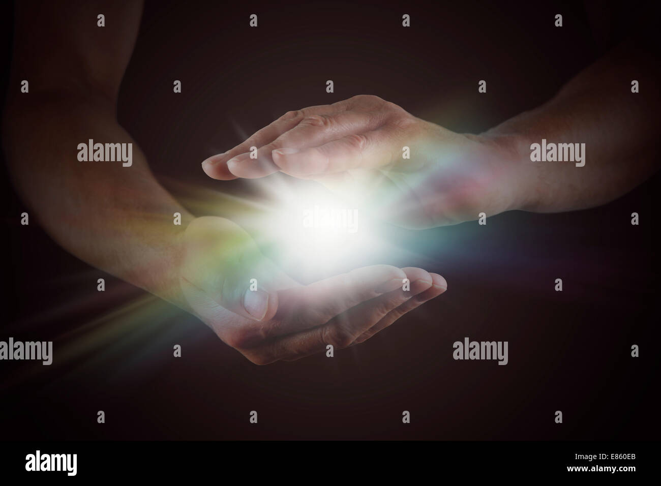Male hands emerging from darkness, cupped, with rainbow colored bright white star burst of light between - Stock Image
