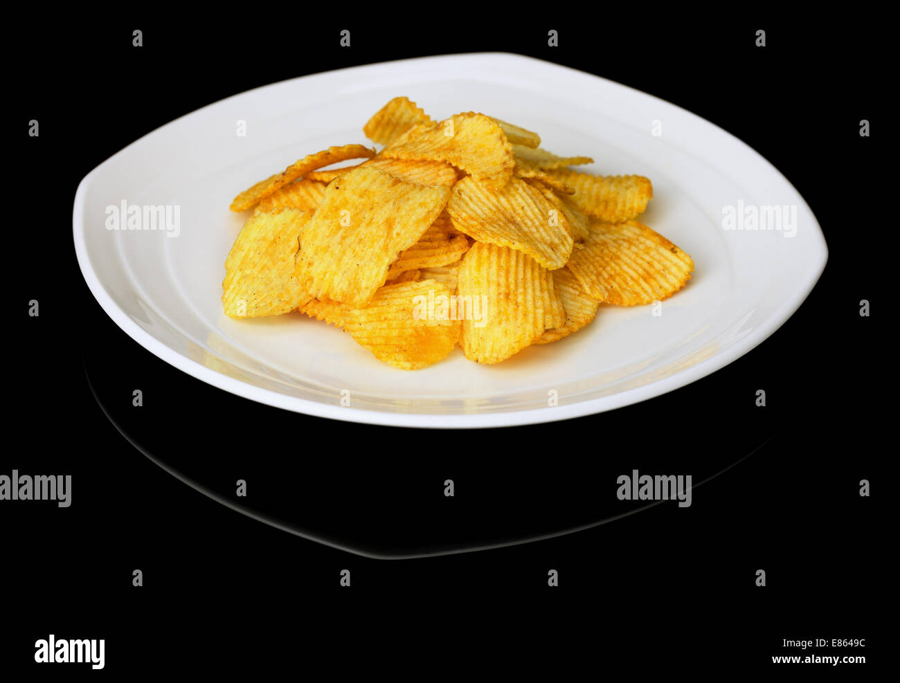 Potato chips on a plate on a deep black background - Stock Image