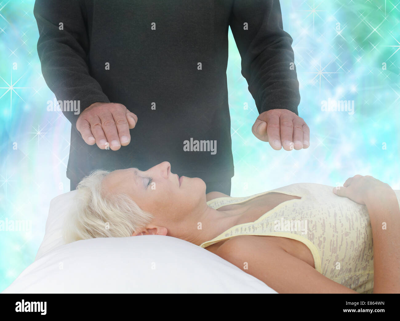 Female lying with eyes closed and male healer with hands hovering channeling energy in misty sparkling green energy - Stock Image