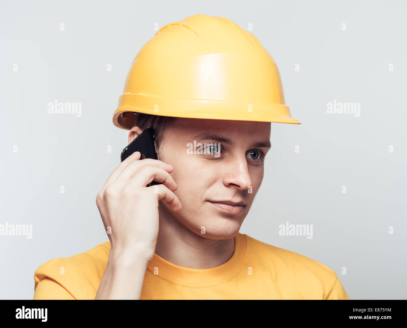 Male worker talking on mobile phone Stock Photo