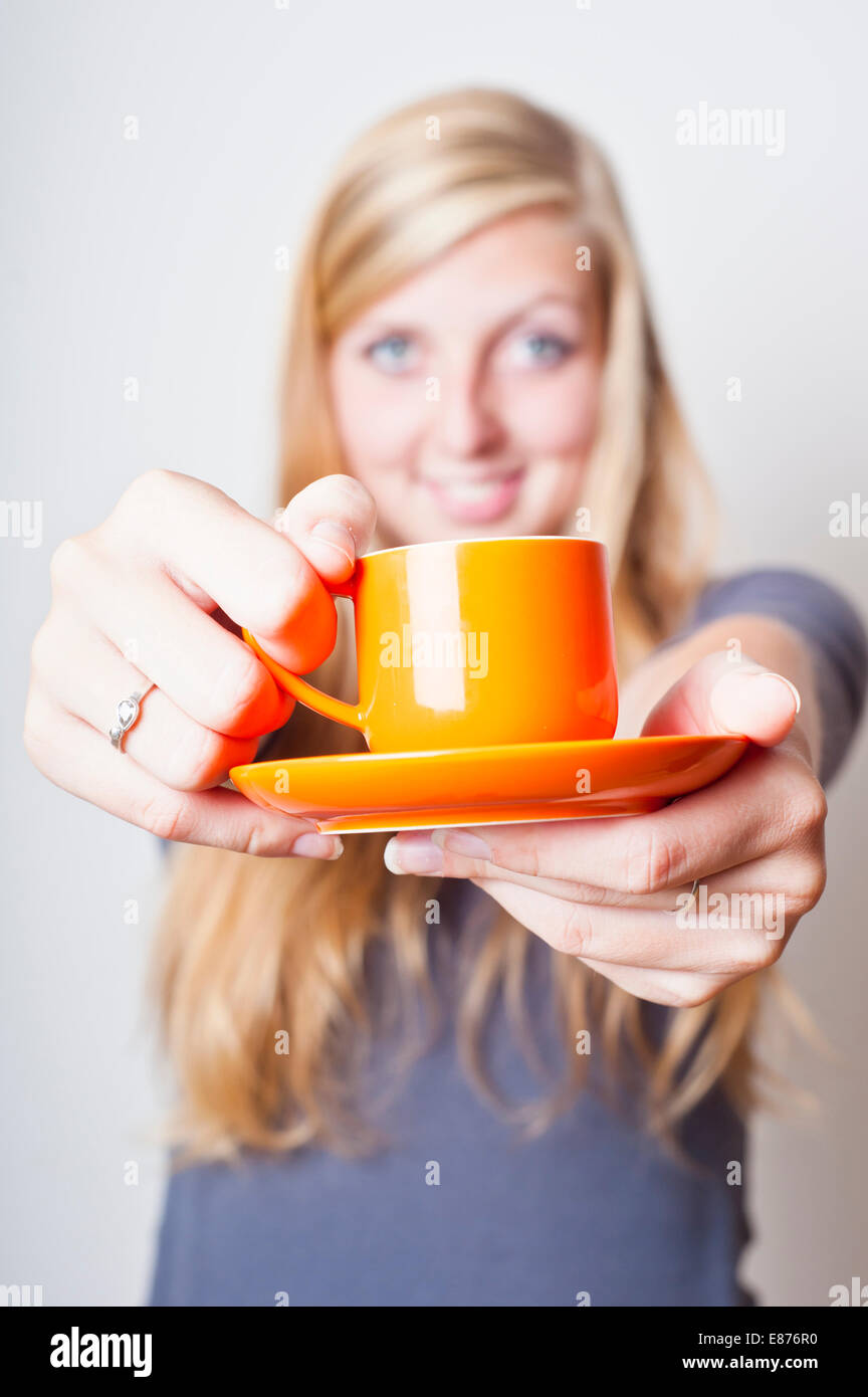 blond teenager girl smiling and offering a cup of coffee - Stock Image