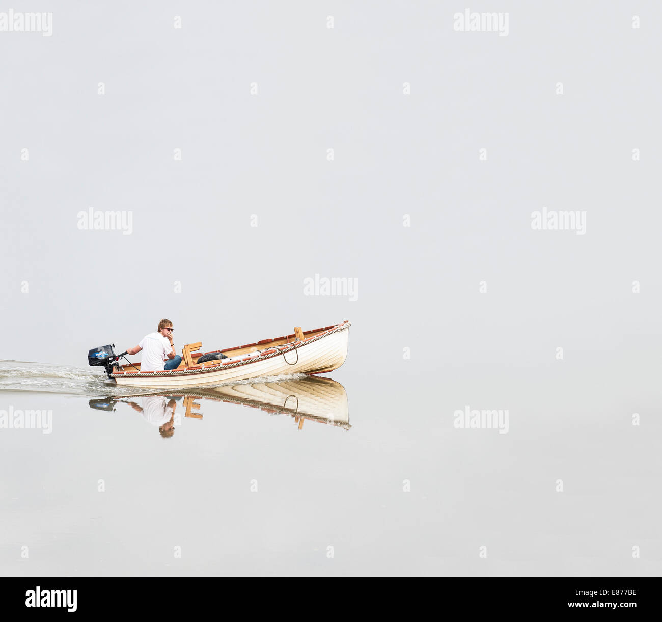 A man steering a small dinghy on a placid Blackwater River in Essex. - Stock Image