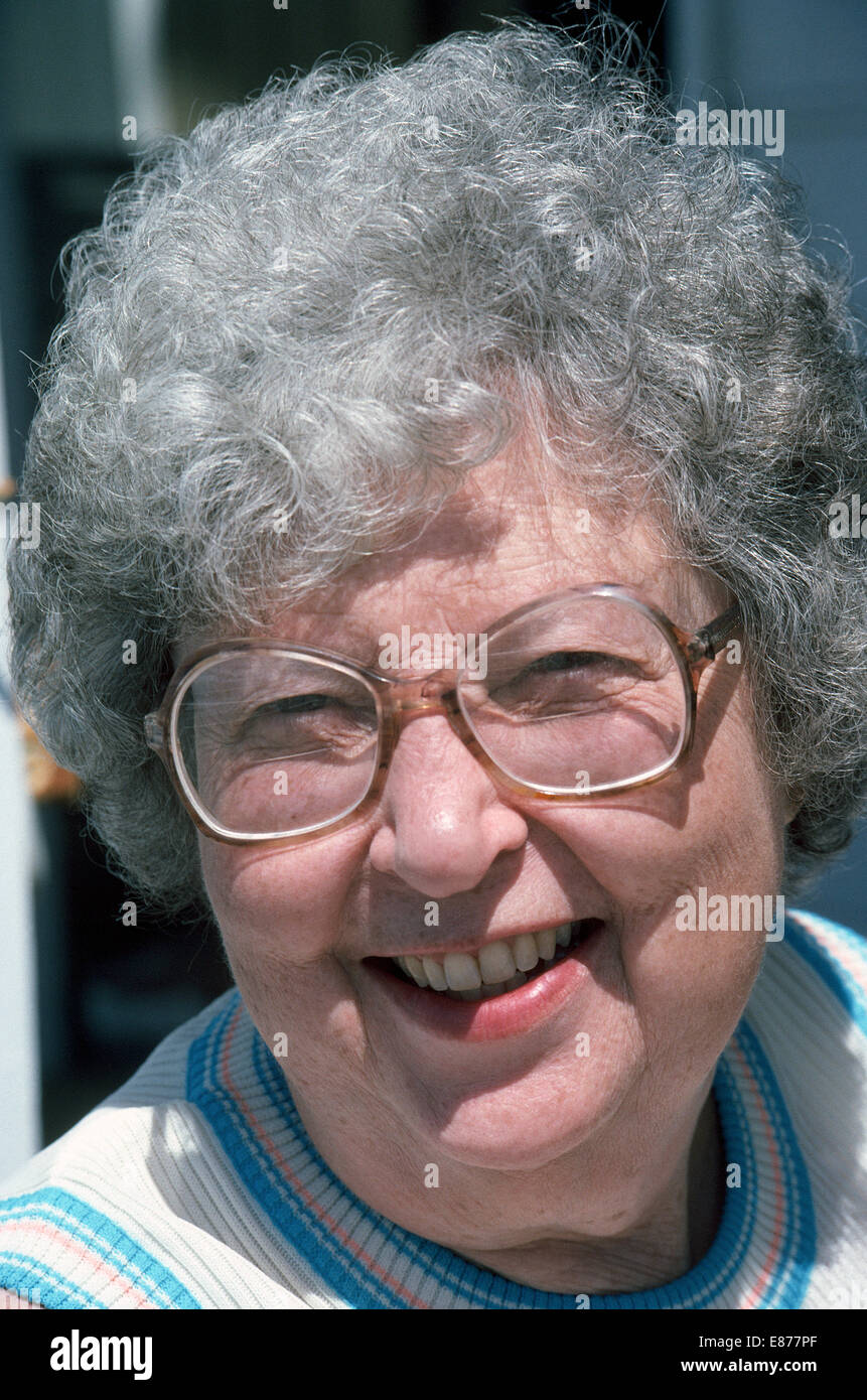 An elderly 70-year-old American Caucasian woman with gray hair and large bifocal eyeglasses smiles in the bright - Stock Image