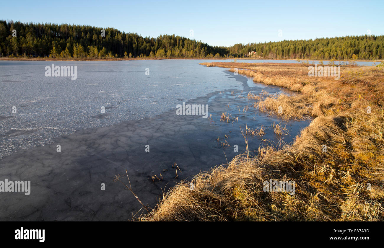 Melting and weak ice on a small forest lake at Springtime , Finland - Stock Image