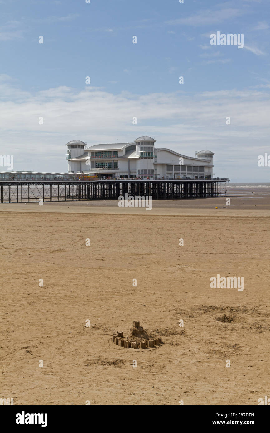 The Grand Pier, Weston-super-Mare, Somerset, England, with a sandcastle in the foreground Stock Photo