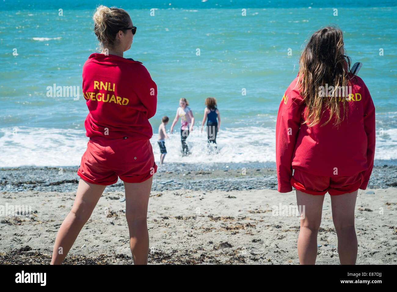 ef2c33be100 Two young women RNLI lifeguards on Aberystwyth beach watching children  playing in the sea