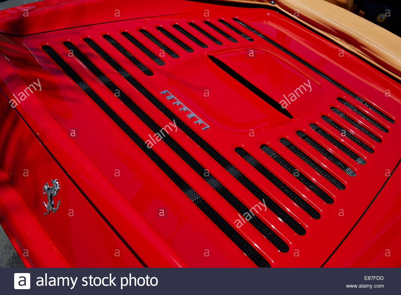 Chrome Ferrari badge on a bright red 355 engine cover - Stock Image