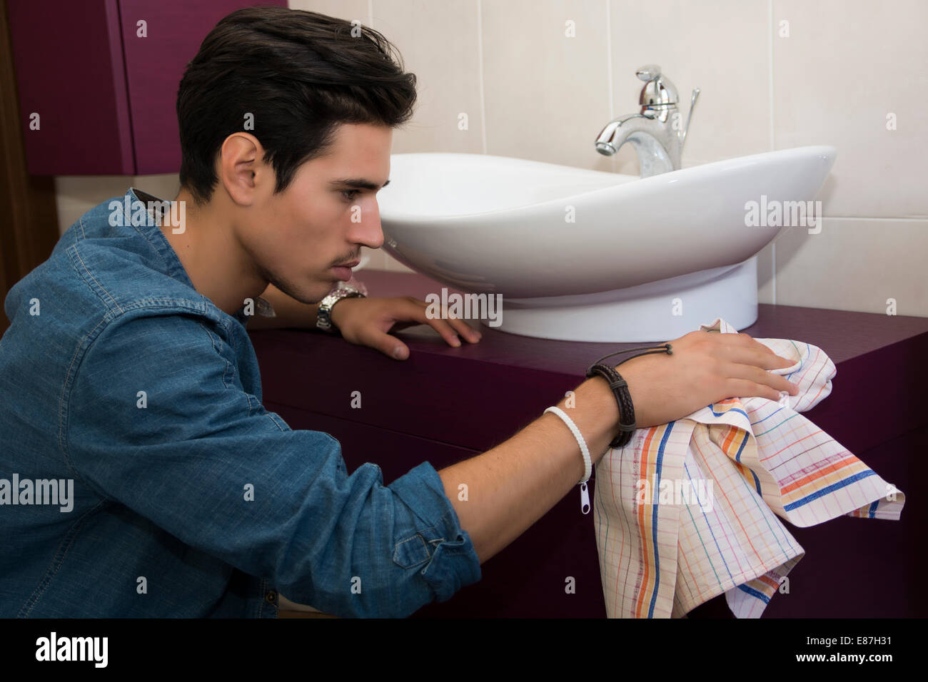 Handsome young man kneeling down with a cloth in his hand cleaning the bathroom interior wiping the ceramic hand - Stock Image
