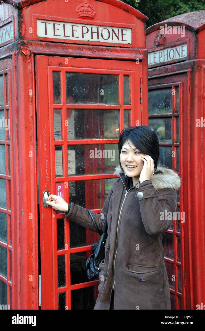 young Japanese woman using mobile phone outside a traditional red telephone box, England, UK - Stock Image