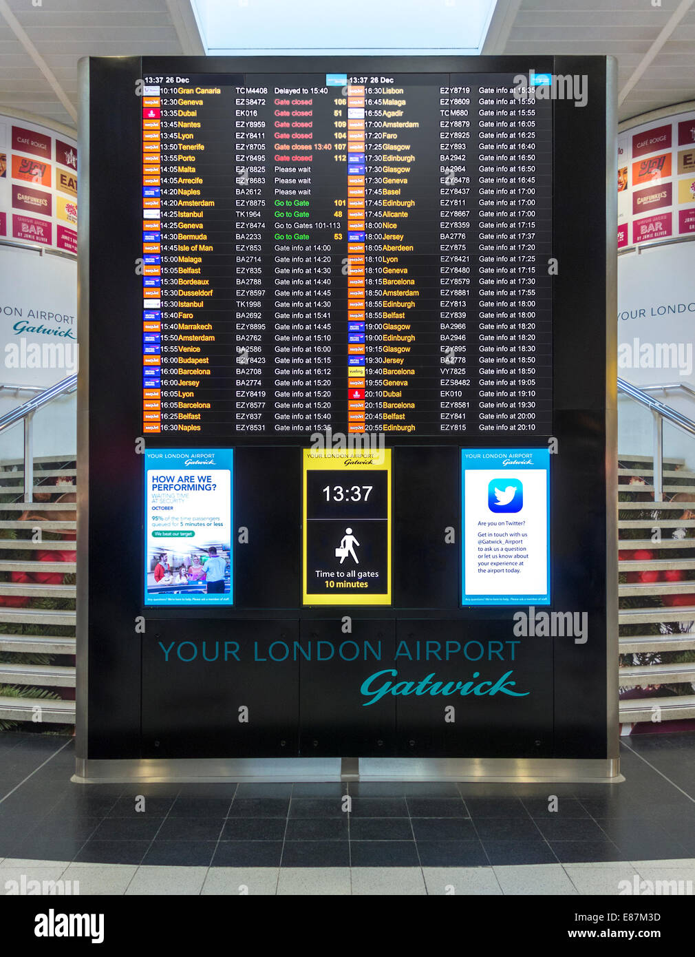London Gatwick North Terminal gates info and flight departures board. Walking distances sign, clock, Twitter announcement. - Stock Image