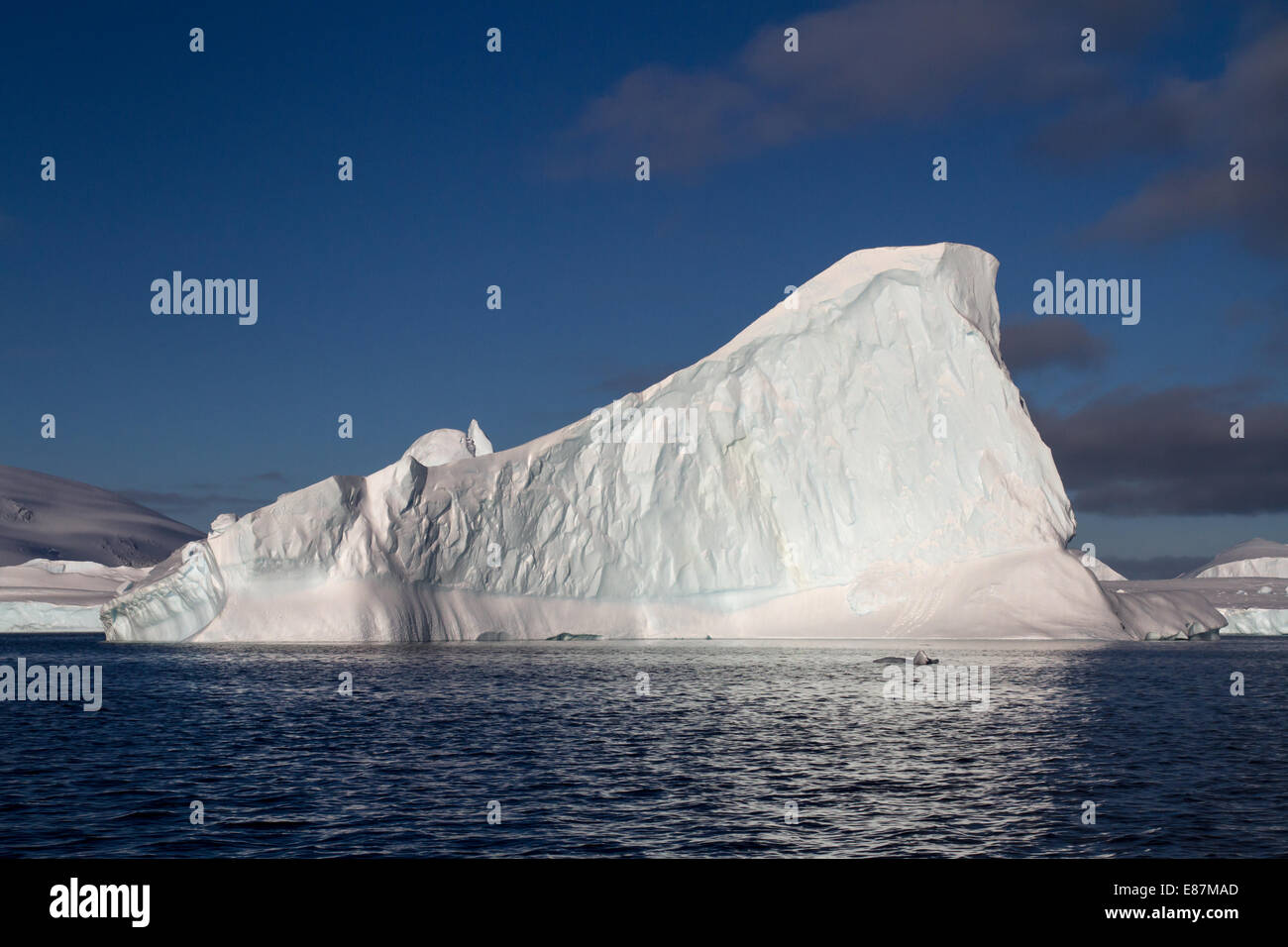 triangular iceberg in Antarctic waters summer cloudy day - Stock Image