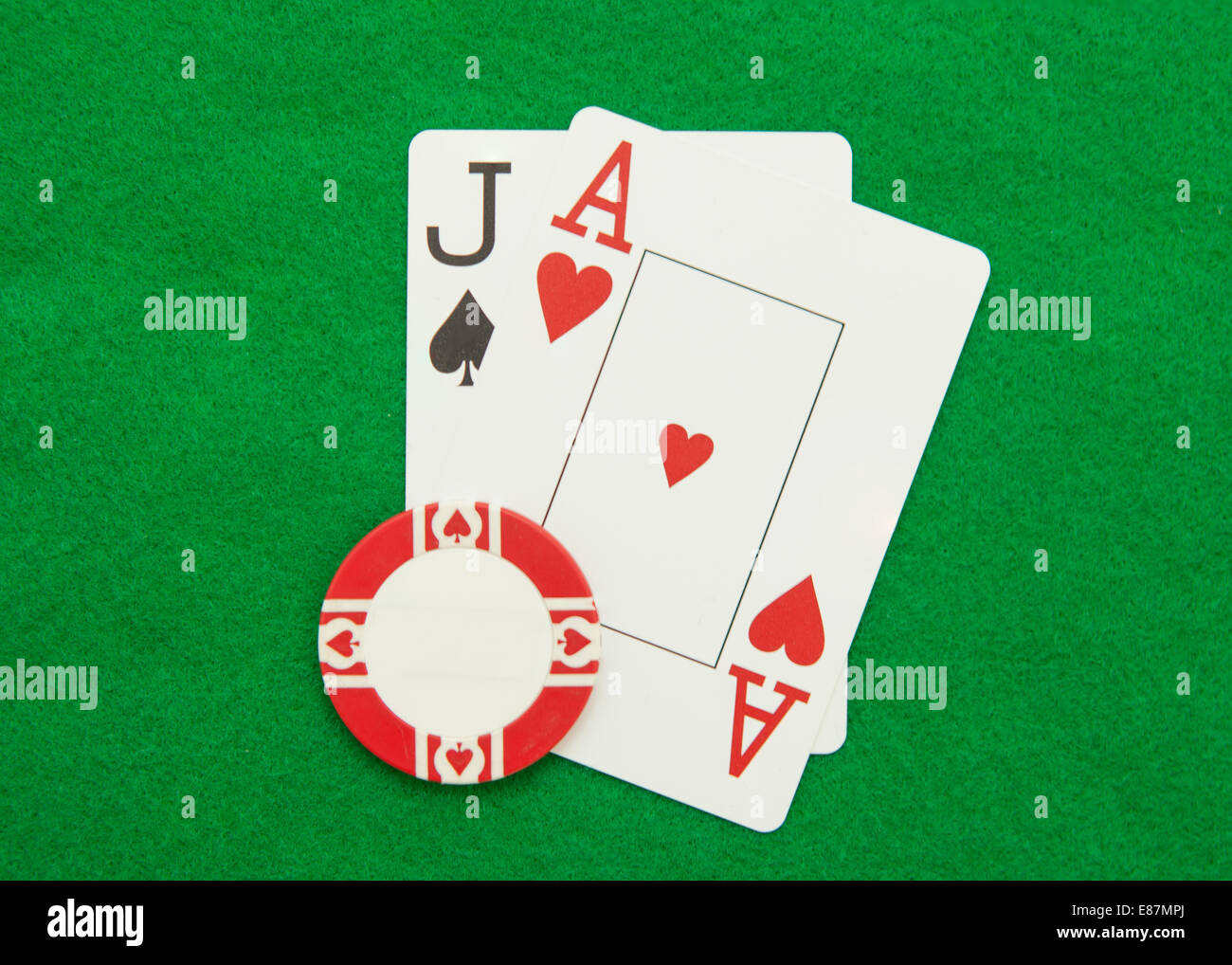 Blackjack hand with casino chip on green casino table - Stock Image