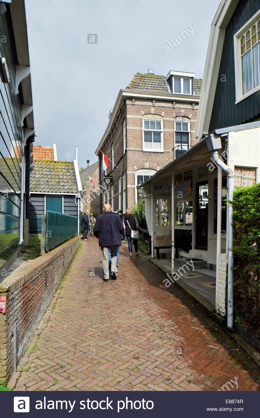 People walk on the narrow Buurt II by the Hof van Marken on the island/peninsula of Marken, The Netherlands. - Stock Image