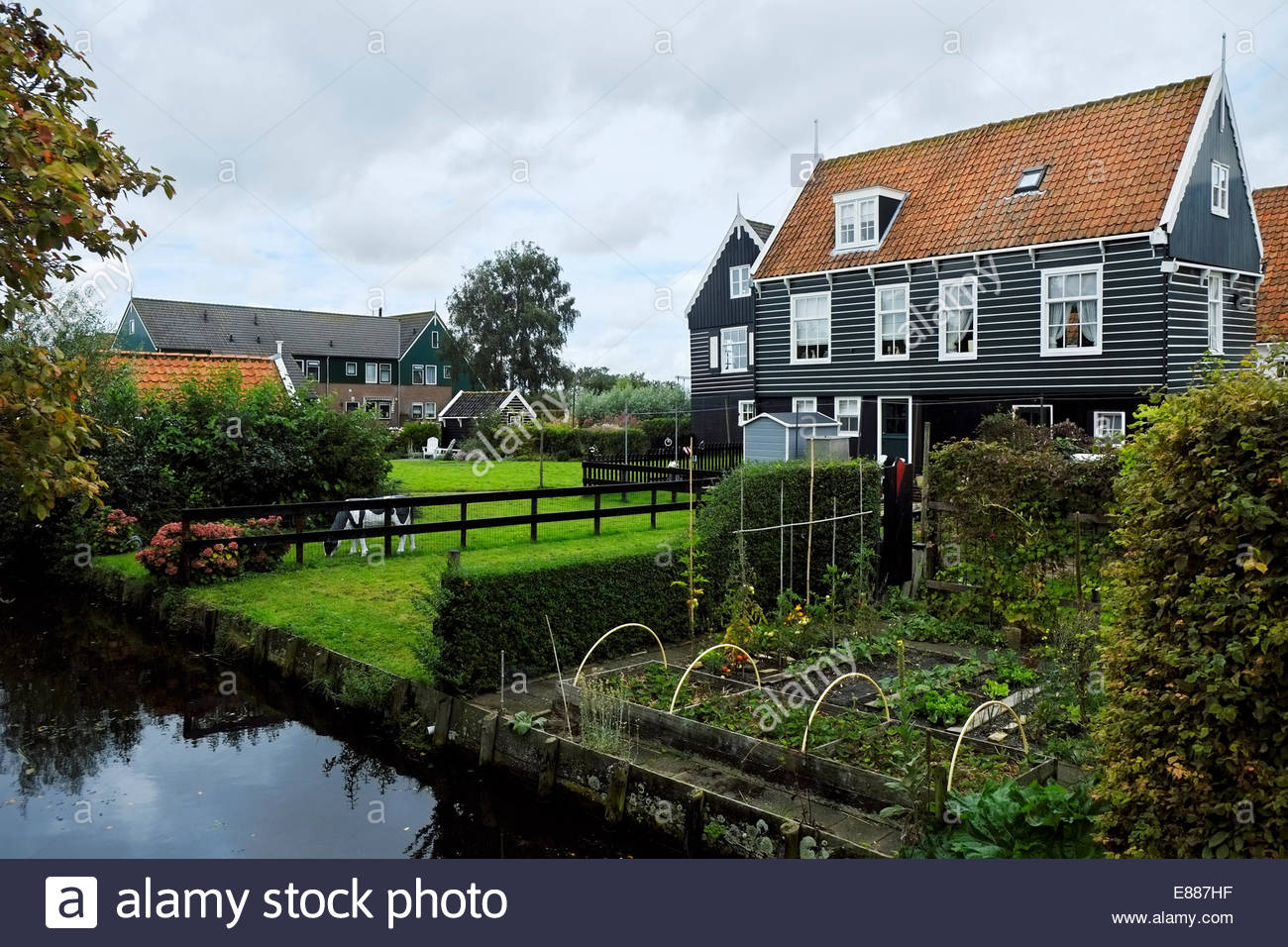 Traditional houses and gardens with added animal figures on the island/peninsula of Marken, The Netherlands. - Stock Image