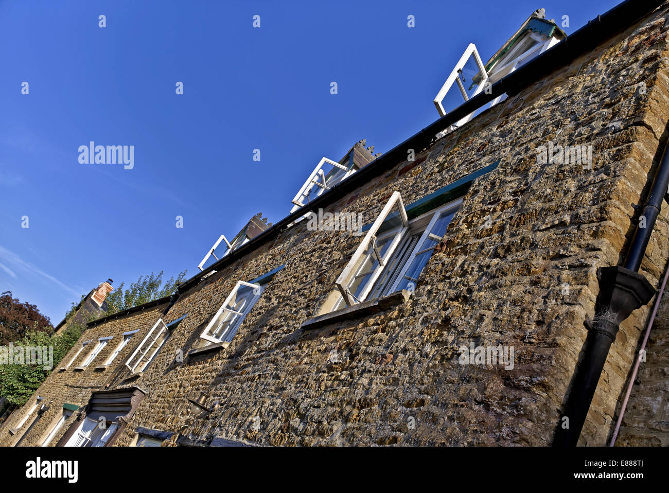 Cotswold stone cottages and wood framed windows against a bright blue sky on an glorious summer day. England UK - Stock Image
