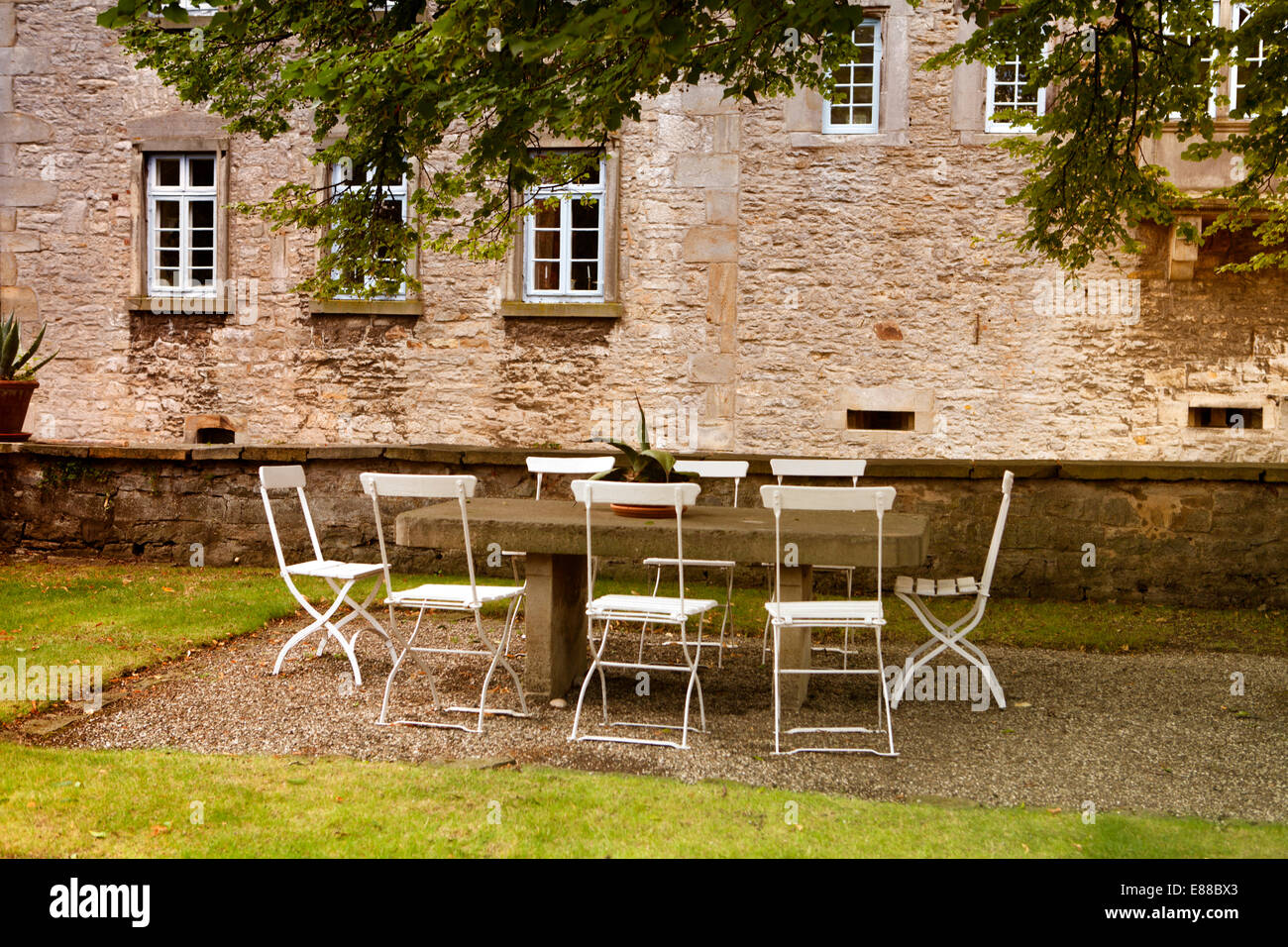 Chairs and tables outside, Schloss Huelsede, moated Castle in Huelsede, Weser-Renaissance, Lower Saxony, Germany, - Stock Image