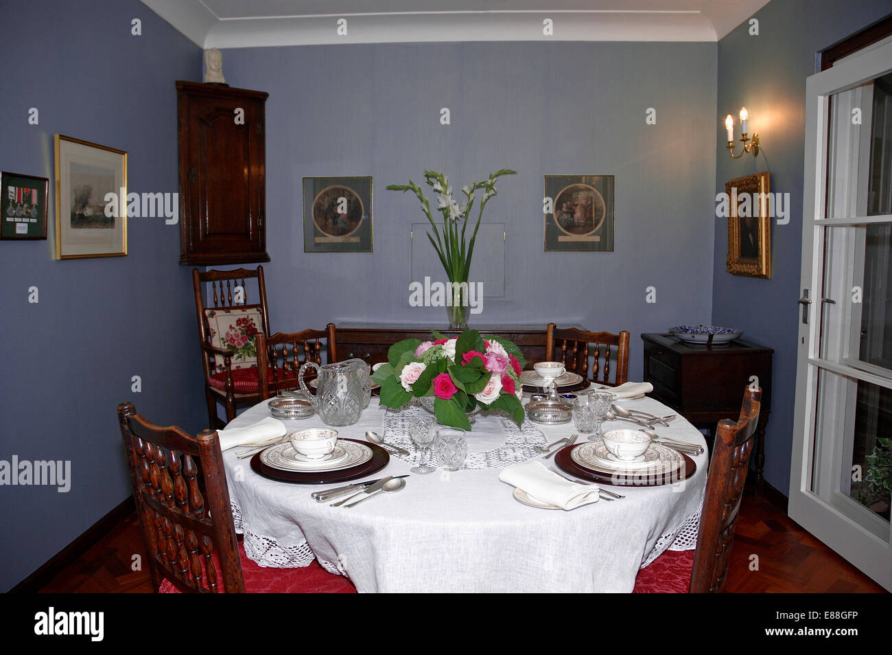 Place settings and white cloth on table in small blue diningroom with wall lights - Stock Image