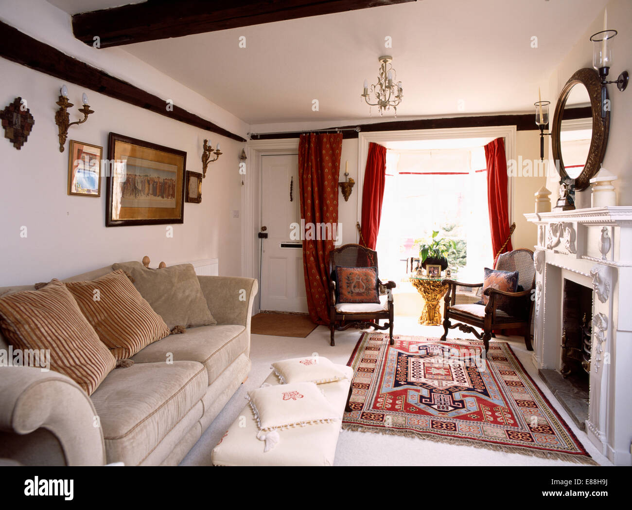 Patterned rug and beige velour sofa in country living room ...