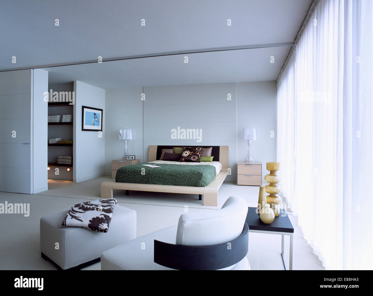Simple Wooden Bed In Large Modern Bedroom With White Flooring And Leather Chair Stool