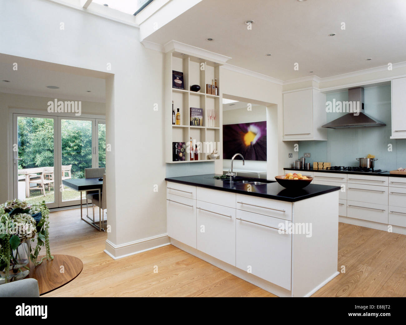 Black granite worktop on peninsular unit in modern white kitchen ...