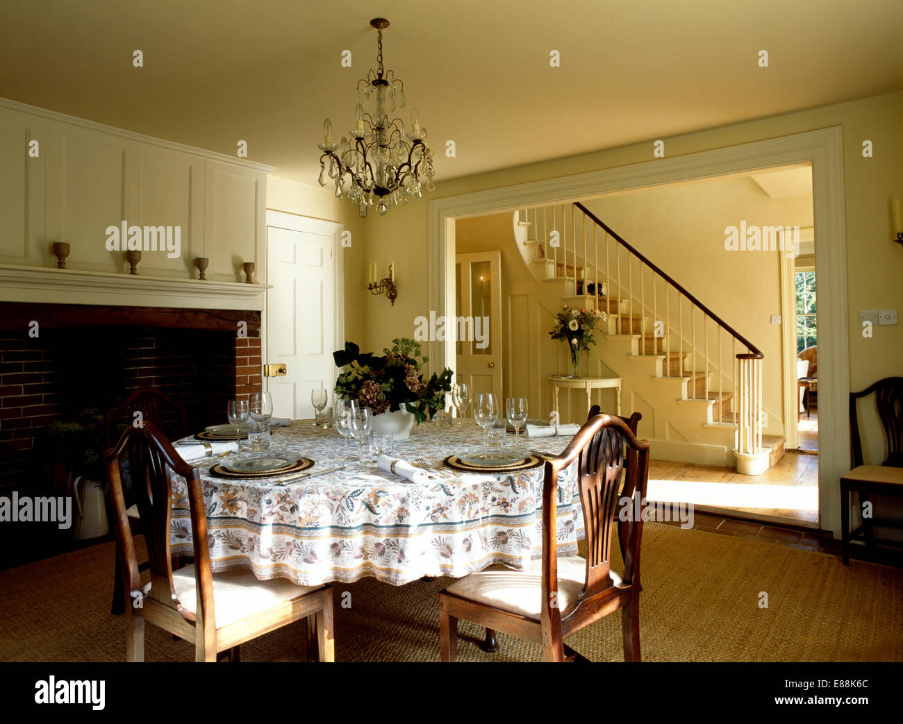 Place settings and floral cloth on table in country dining room with double doorway to hall - Stock Image