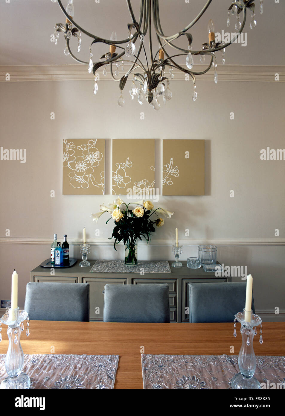 Stylised modern triptych pictures in dining room with metal chandelier above light oak table with grey suede chairs Stock Photo