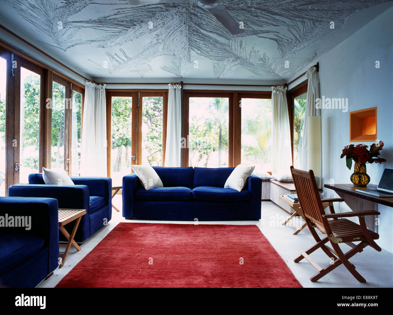 Blue Sofas And Large Red Rug In Modern White Caribbean Living Room With Textured Ceiling