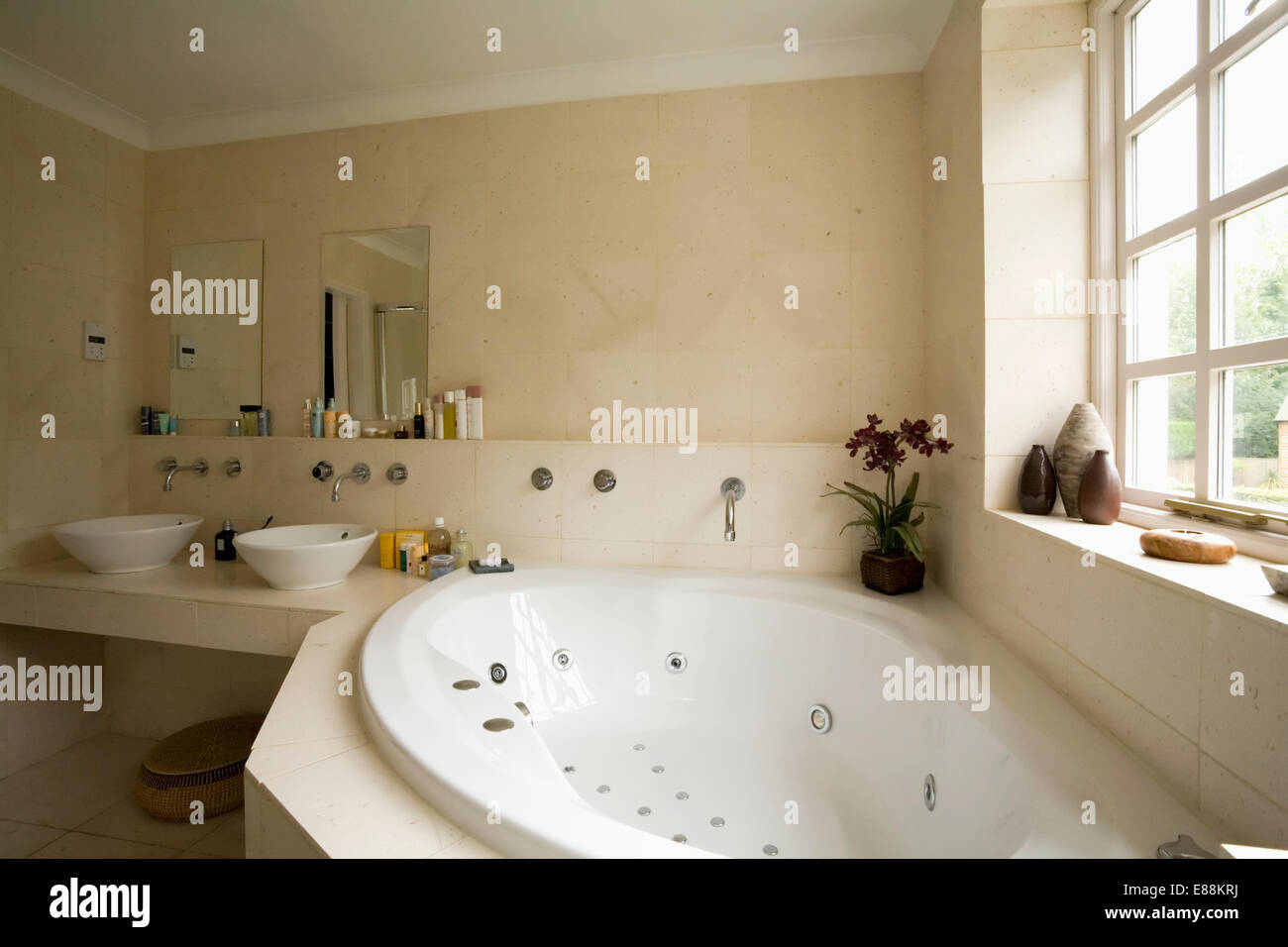 Corner jacuzzi bath below window in modern bathroom with limestone