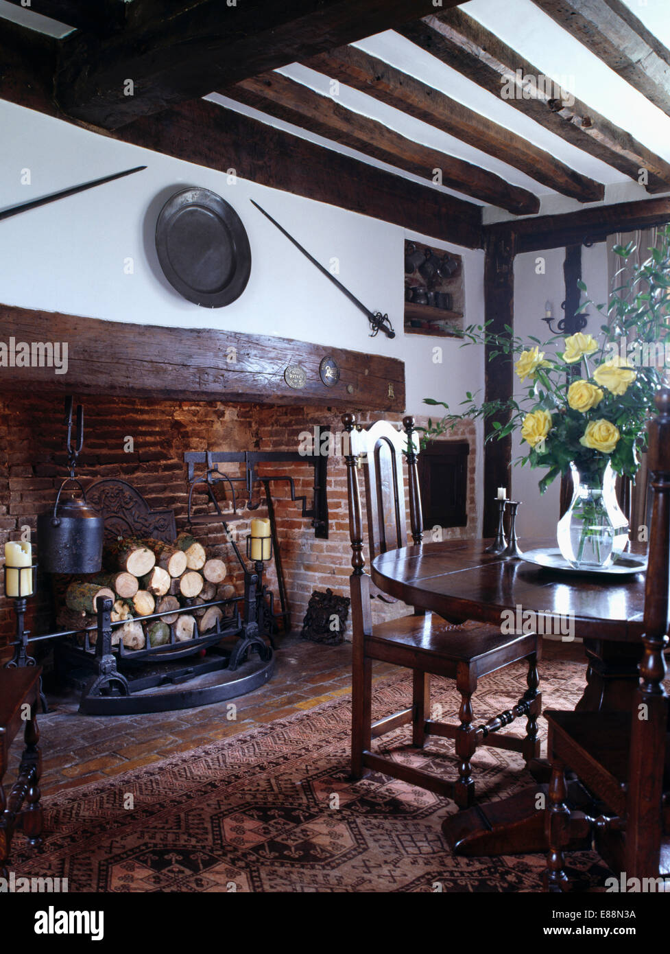 Polished oak reproduction chairs and table in country dining room with Tudor inglenook fireplace - Stock Image