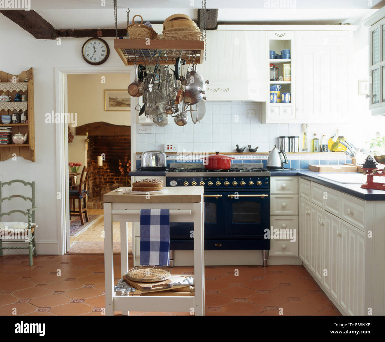 metal utensils on ceiling rack above butcheru0027s block in white country kitchen with terracotta tiled floor butcher a37 country