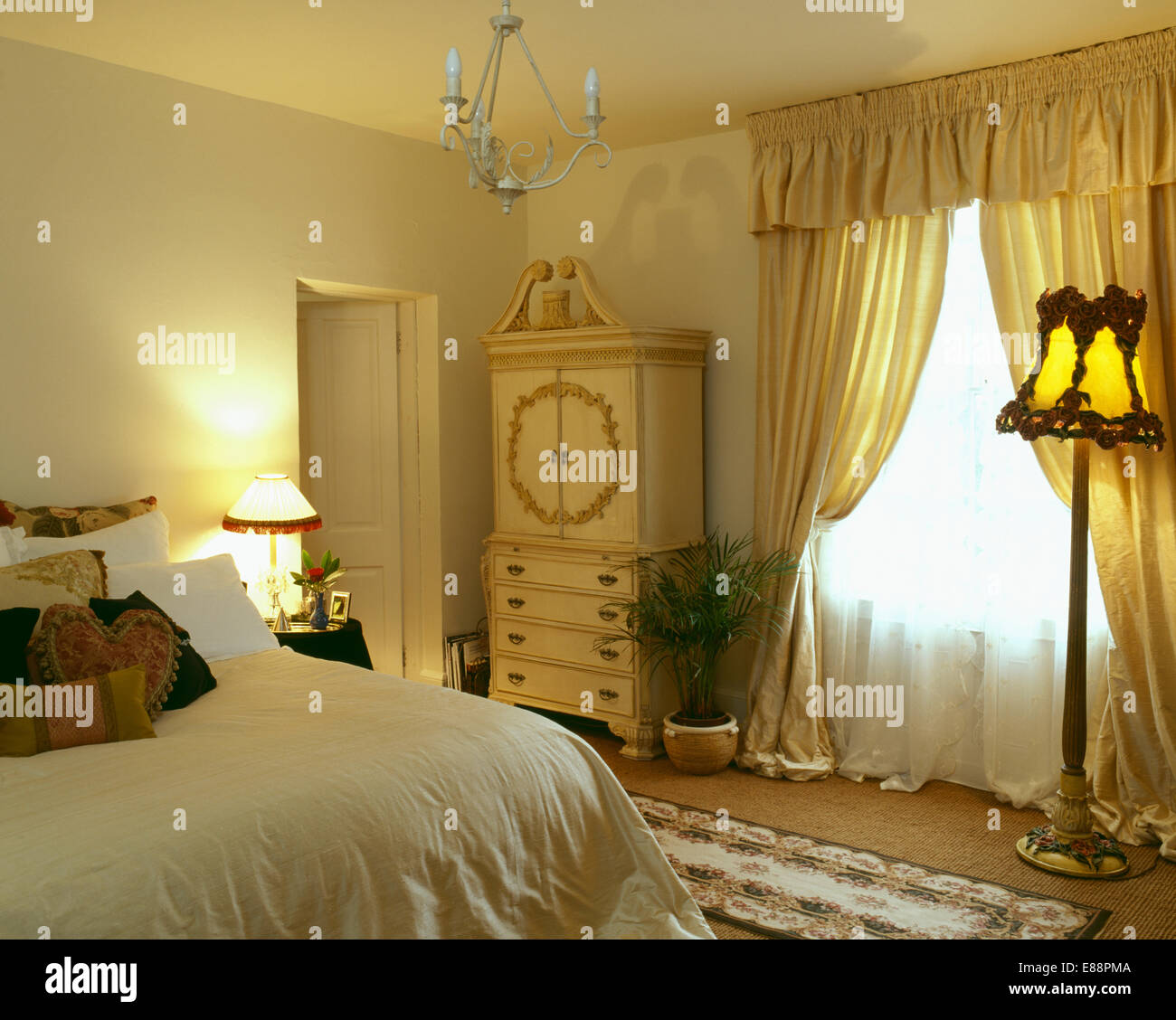 White Voile And Yellow Silk Curtains On Window In Pale Bedroom With Lighted Standard Lamp Cream Cupboard